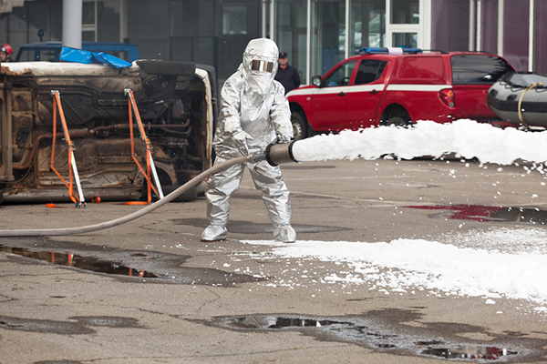 Fully hazard-suited firefighter cleaning up a toxic substance spill